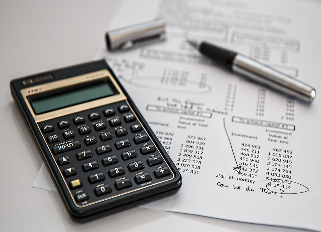 A calculator and pen on top of a balance sheet