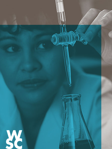 An african american woman dressed in a lab coat overlooking a buret and flask.