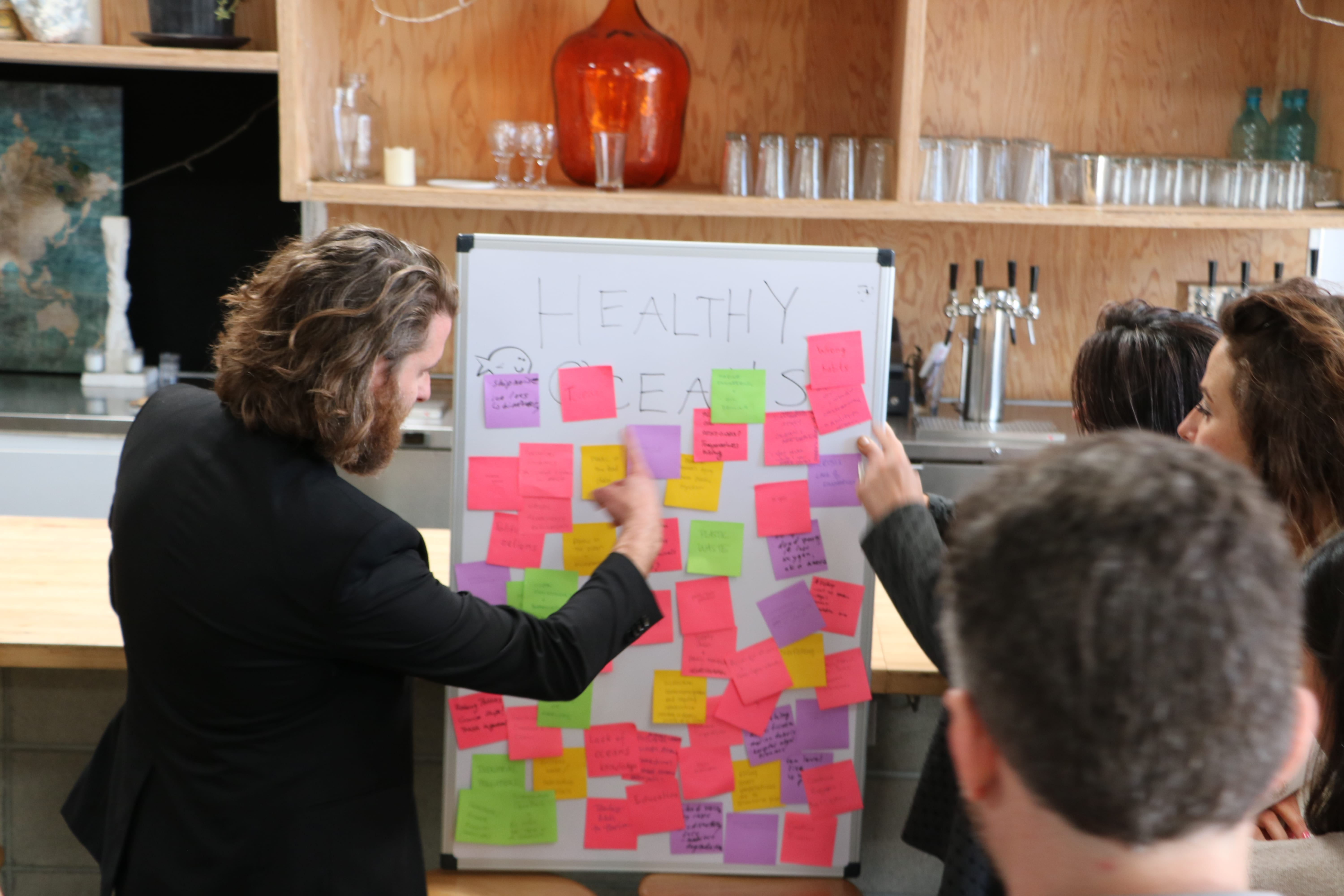 group session with woman looking at sticky notes on a whiteboard