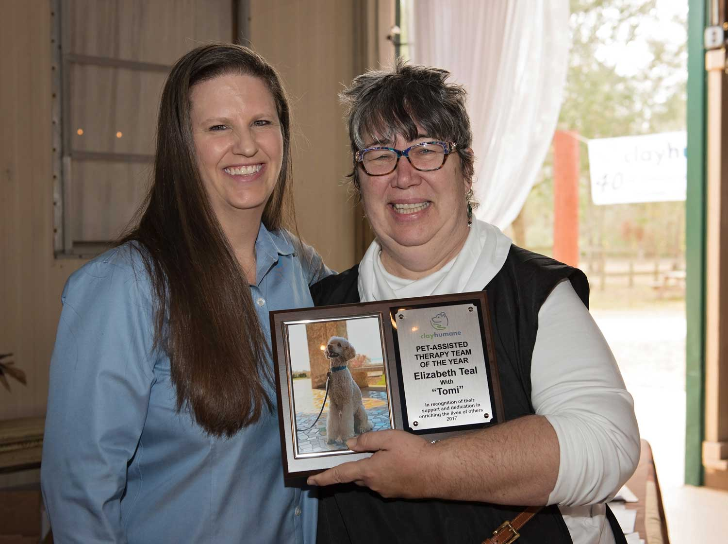 Elizabeth Teal accepts award from Lori Coleman of Clay Humane