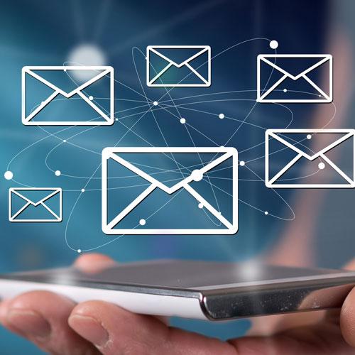 Flygande mail-ikoner ovan telefon i en hand