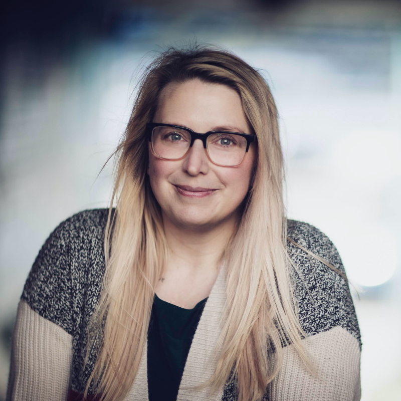 A photo of Mandy Woodland, looking at the camera. She has medium length blond hair, is wearing two toned glasses, and a grey mixed colour cardigan.