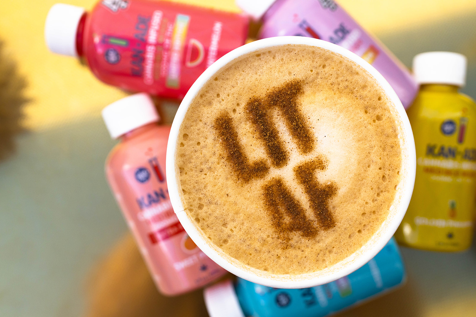 kan+ade bottle background with a cup of coffee with the letter AF written on the foam