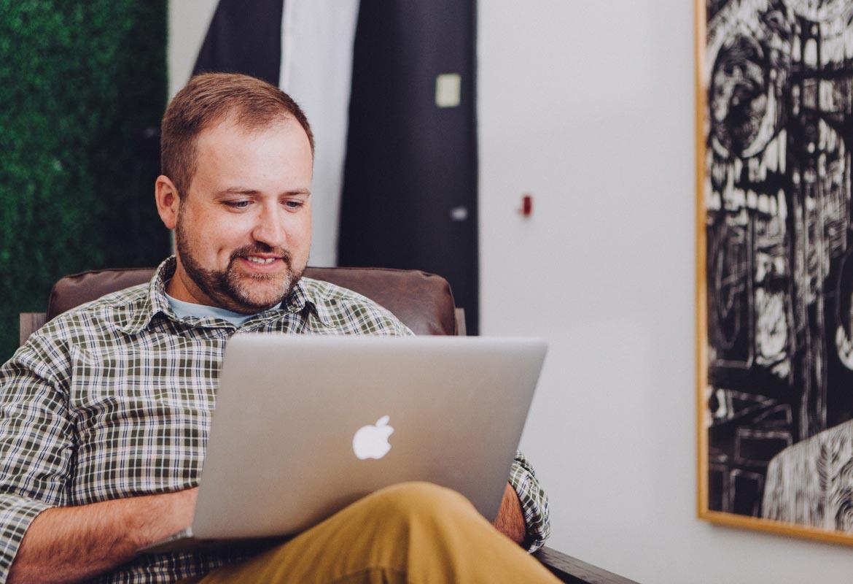 A man sitttng behind his laptop