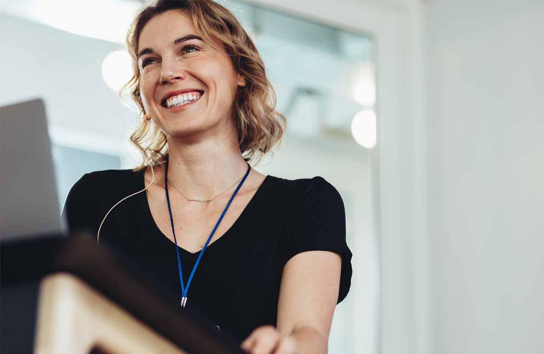 Female office worker sitting at desk, smiling.