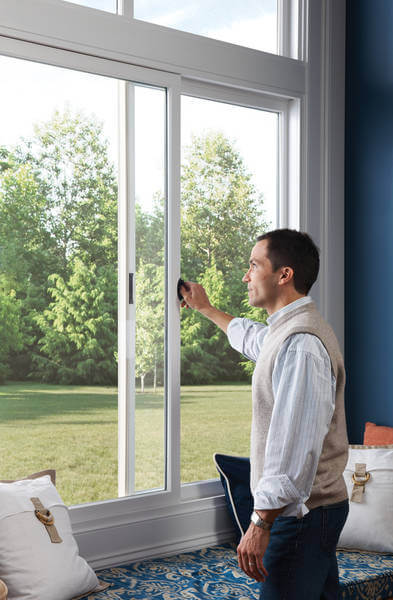 man looking out sliding windows