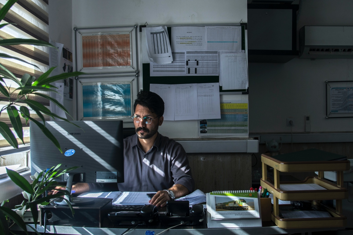 Man sits at desk working_image courtesy of Javad Esmaeili via Unsplash