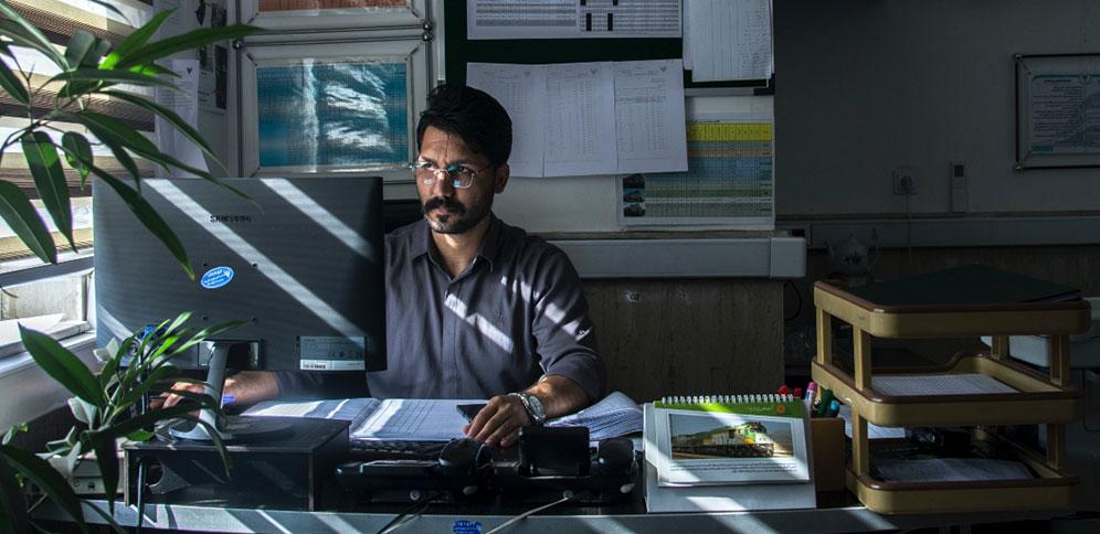 Man sits at desk working_image courtesy of Javad Esmaeili via Unsplash