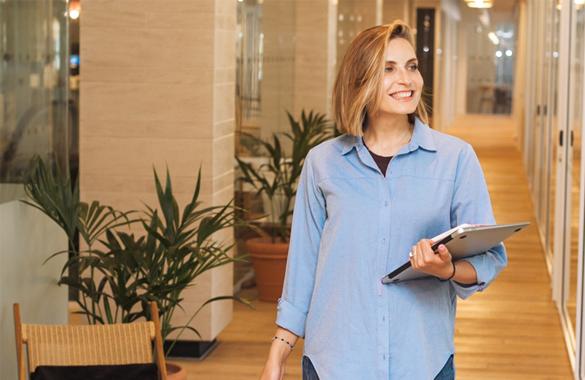 Smiling female employee walks through an office