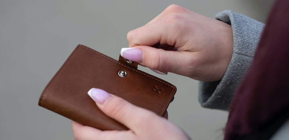 Female hand holding a brown leather wallet.
