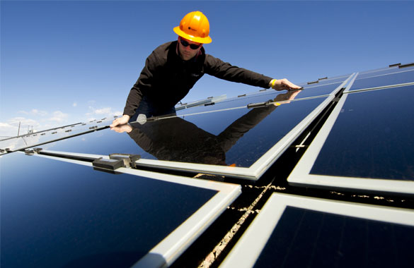 A man installing solar panels on a roof.