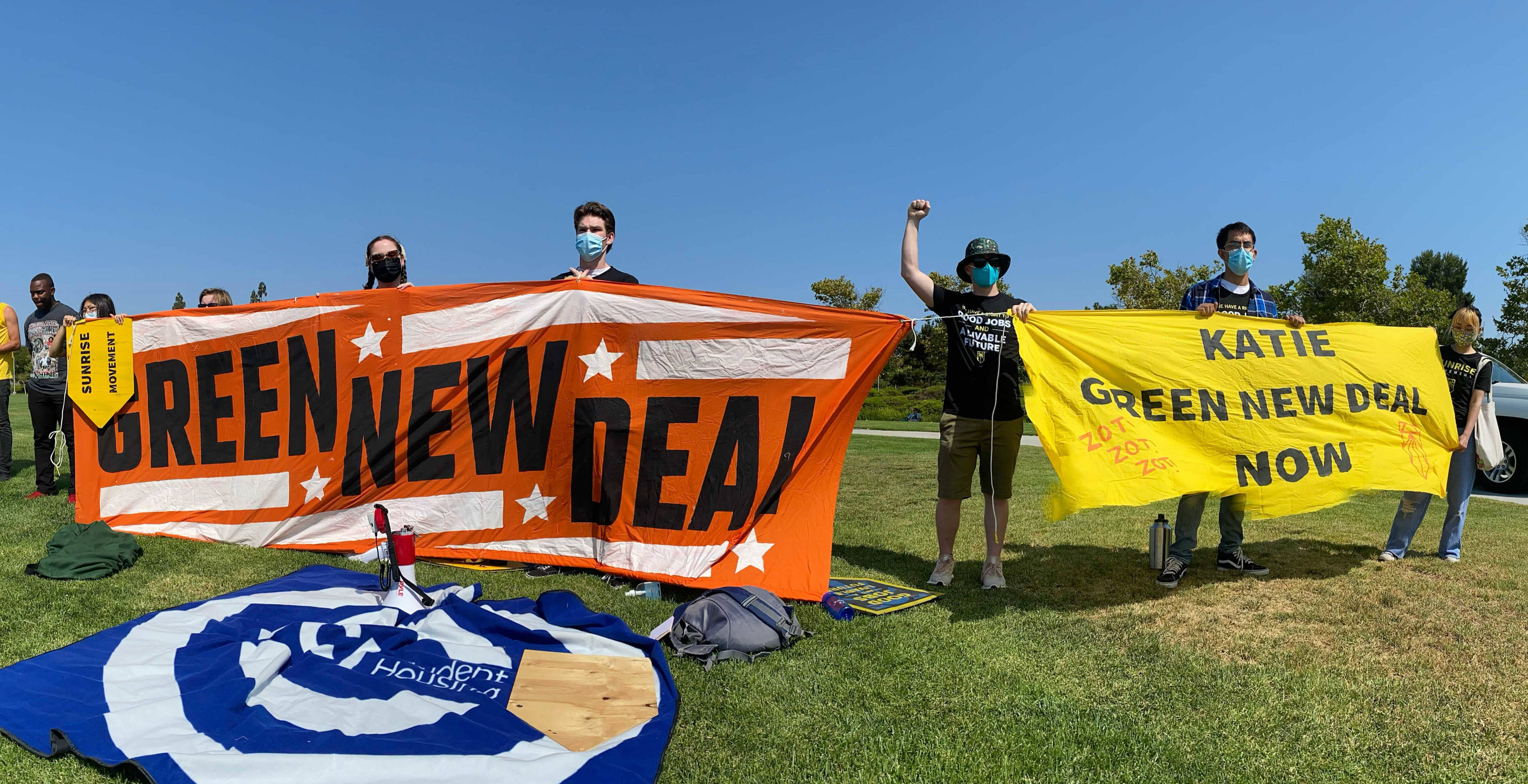 """Sunrise UCI and Orange County Protesters hold up 2 signs outdoors, """"Green New Deal"""" and """"Katie Green New Deal Now"""""""