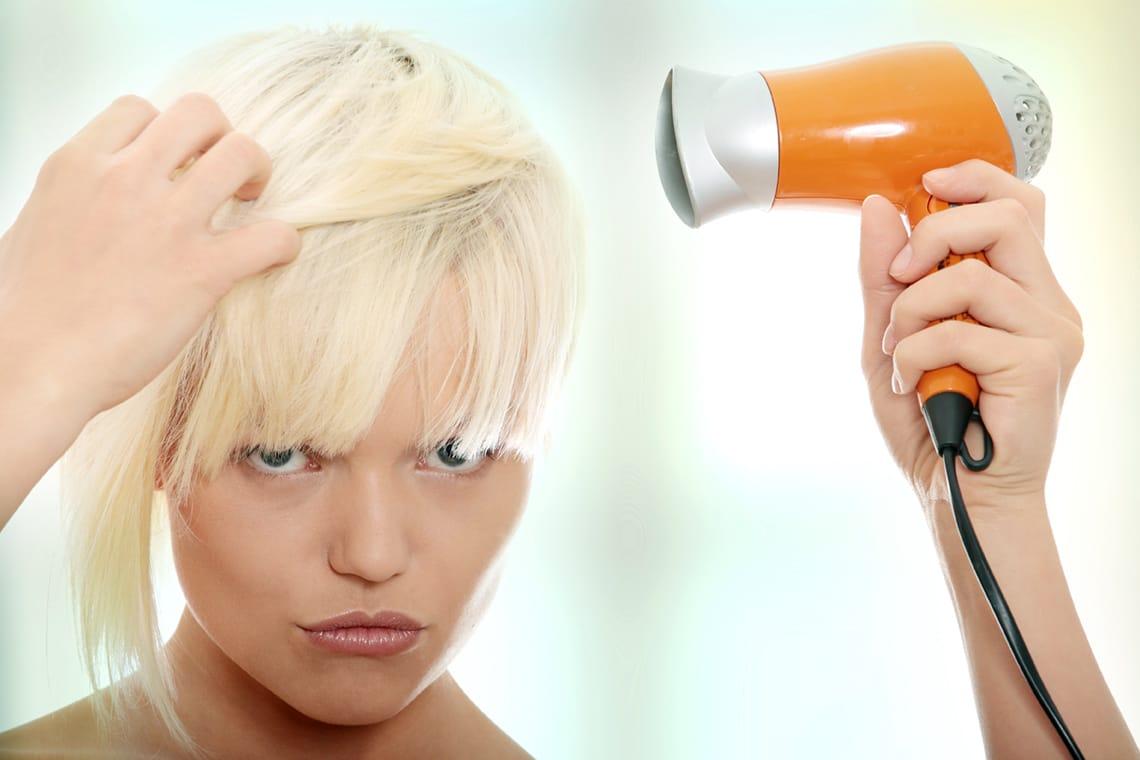 Donna che asciuga i capelli biondi