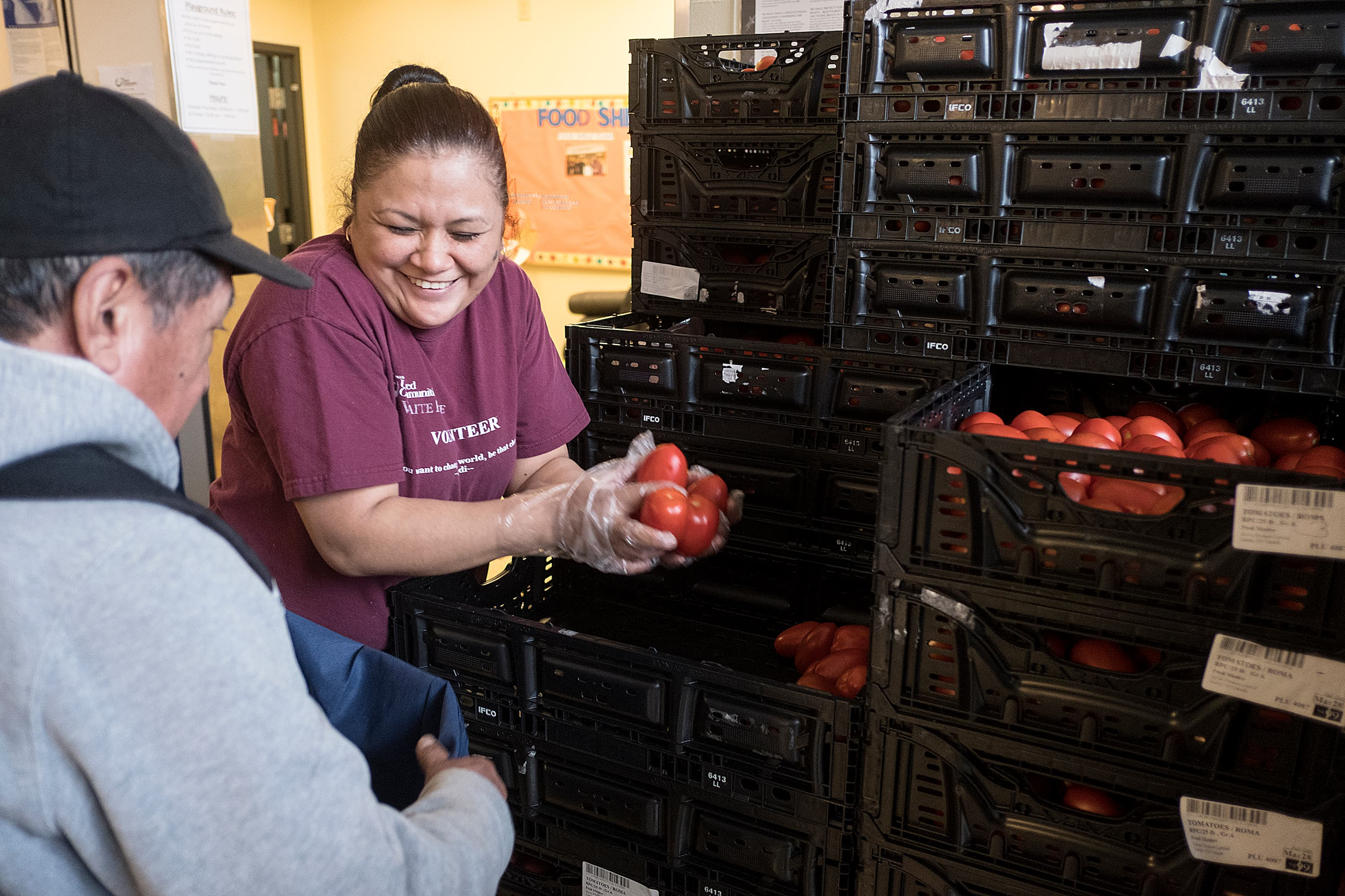 Woman smiling helping distribute tomatoes to someone at a food shelf
