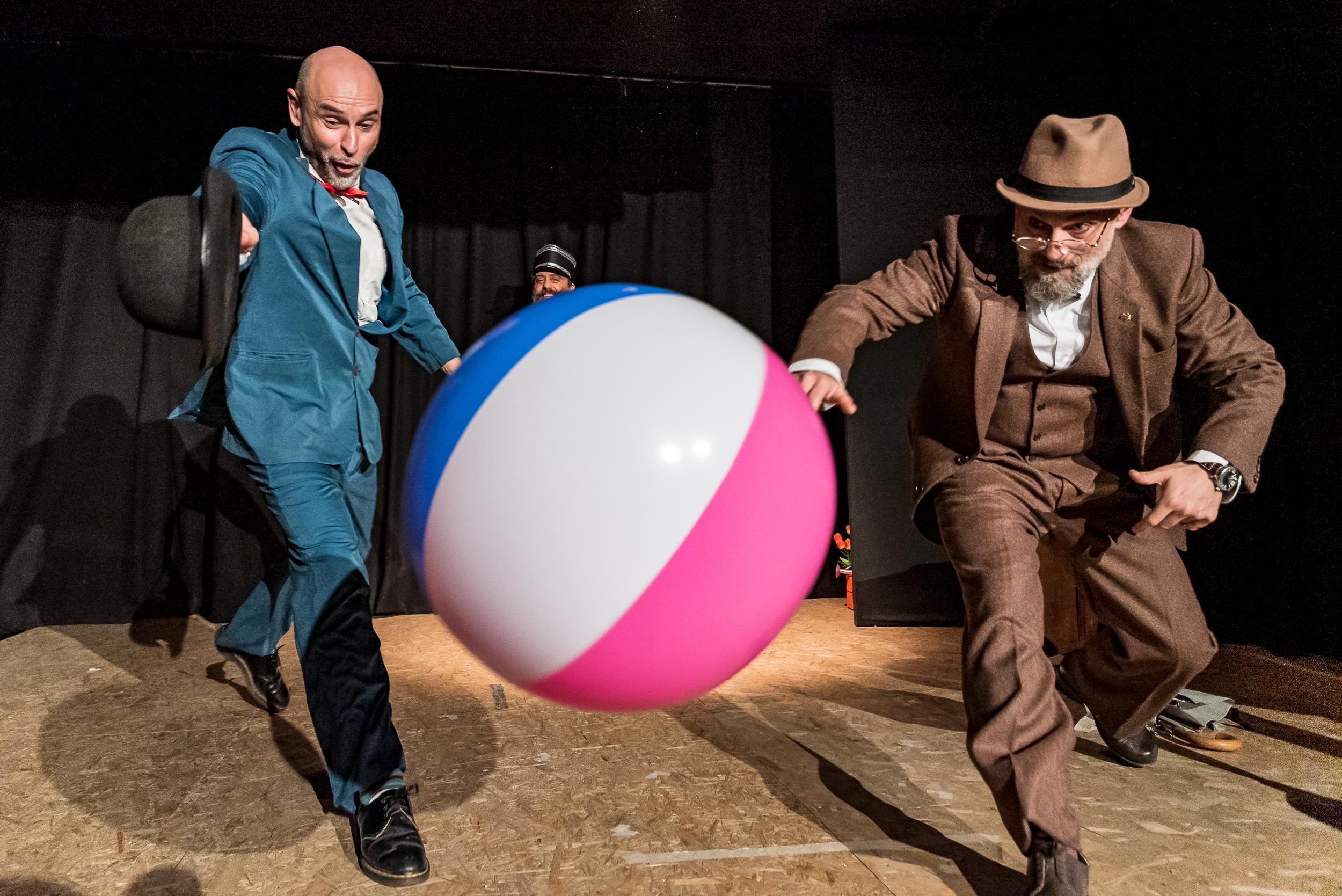 Foto dello spettacolo due uomini, un ombrello e una valigia.