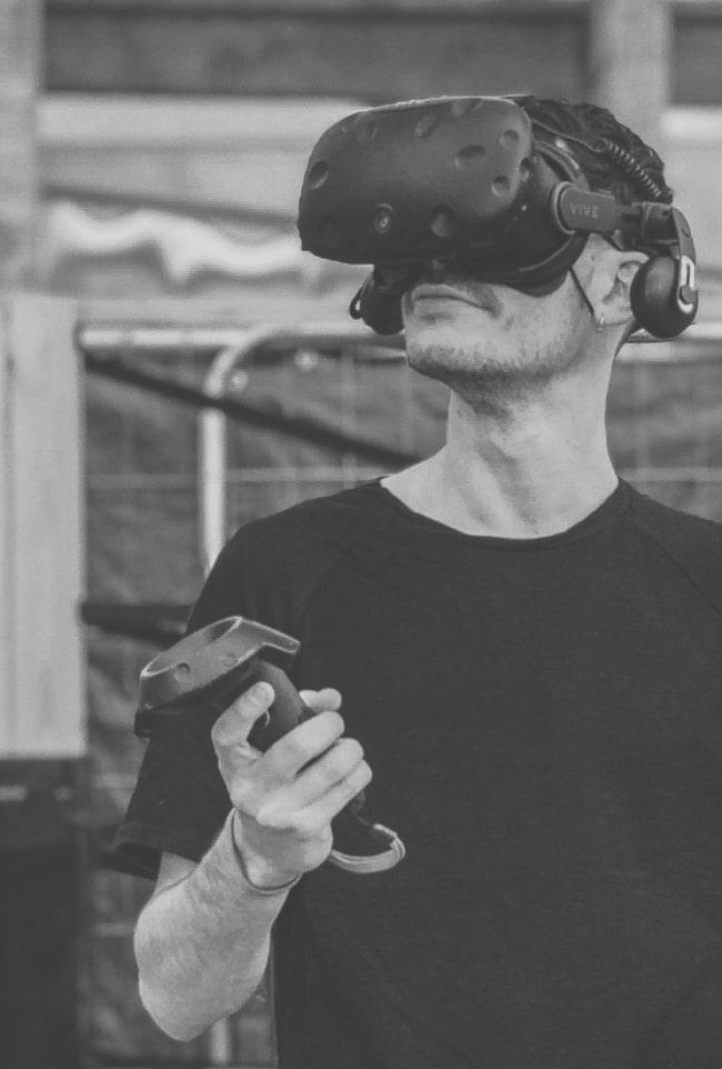 Kevin Bieron essayant un casque de réalité virtuelle lors d'un événement et tenant un joystick dans sa main droite
