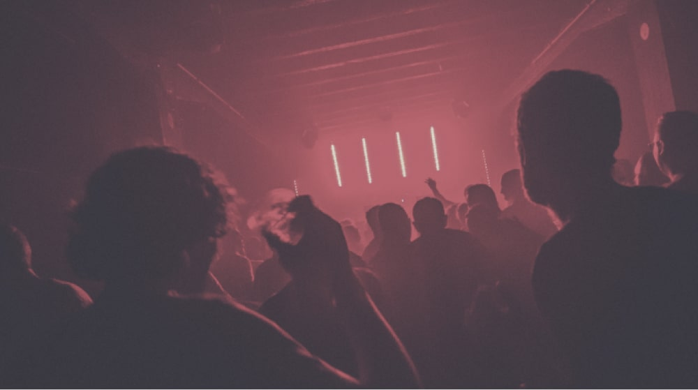 A group of people in a nightclub dancing in a dark room with bright red lights in front of them