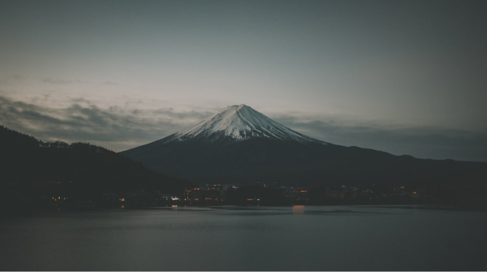 Mount Fuji seen from afar with a city at its foot and a large lake in the foreground