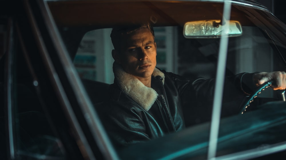 A mannequin posing inside a vintage car wearing a dark brown leather jacket.