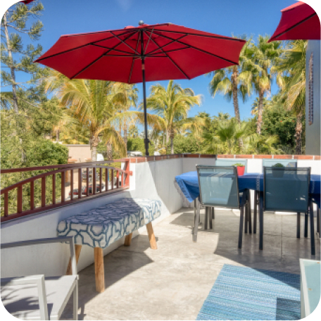 inviting terrace space with red umbrellas and chairs sitting atop a canopy of palm trees