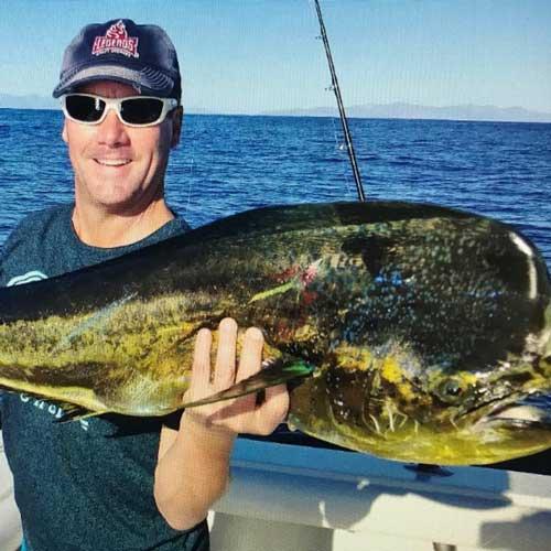 fisherman holding a large dorado on a fishing boat