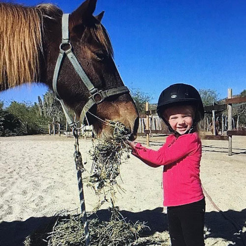 young girl in a pink shirt petting a horse