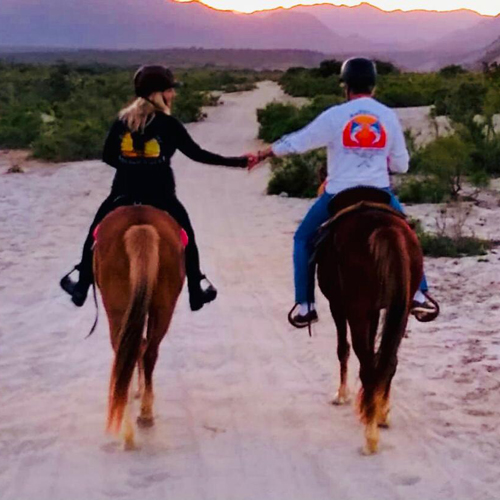 happy couple riding horses on the arroyo into the sunset