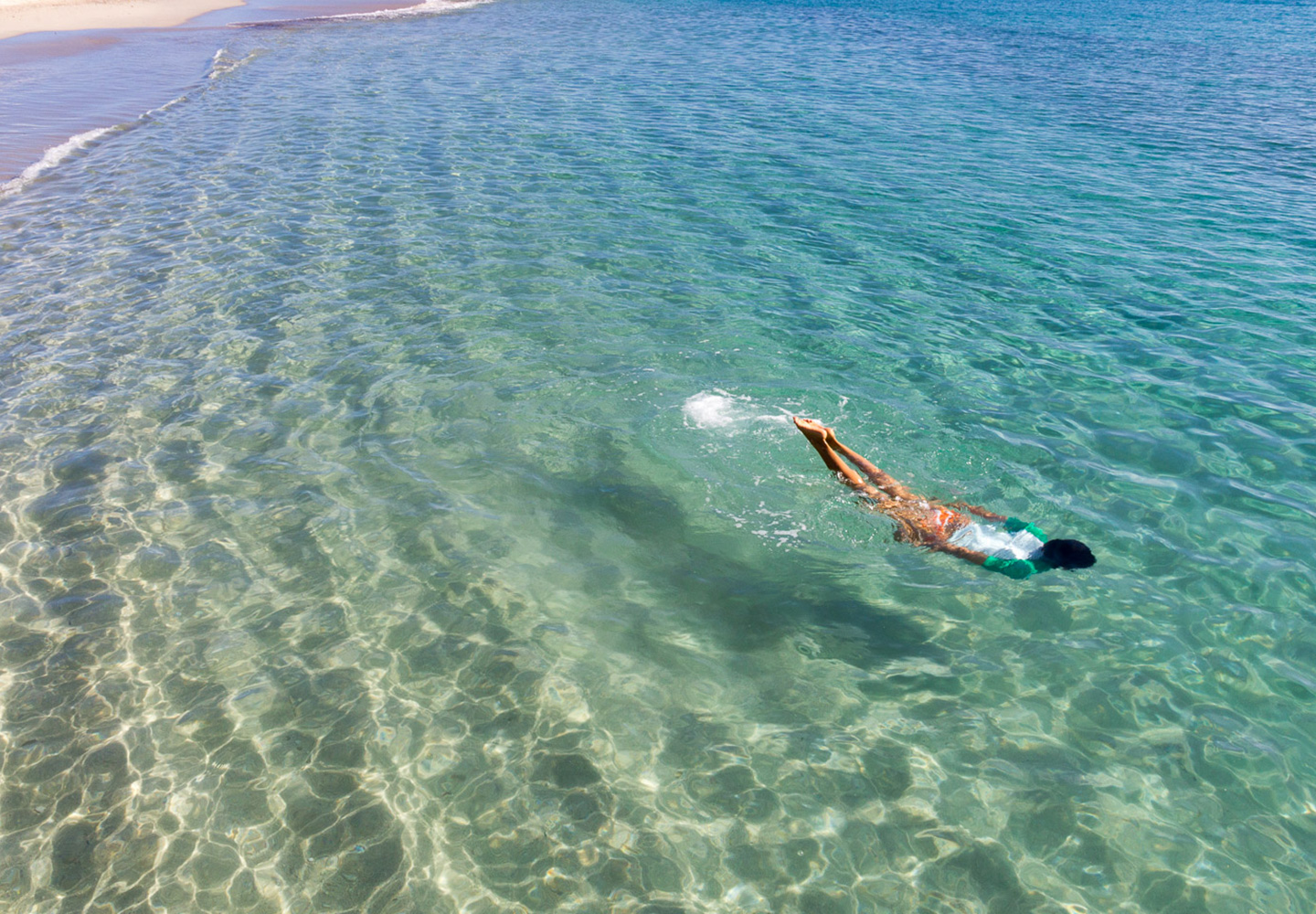 person swimming in crystal clear turquoise water