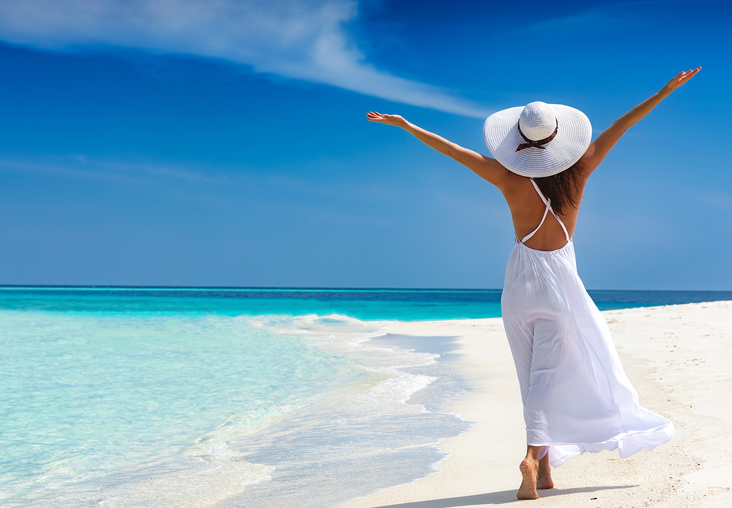 woman with white hat strolling on white sand beach with outstretched arms