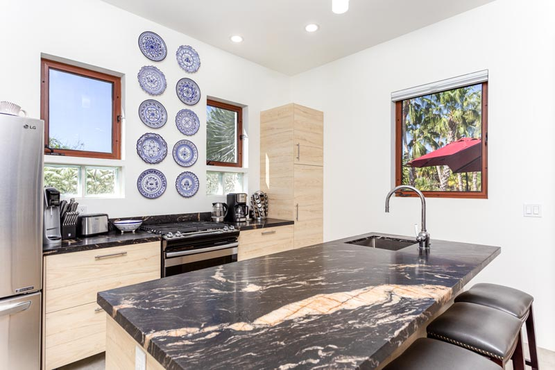 modern white kitchen with dark marbled counters and blue plates on wall