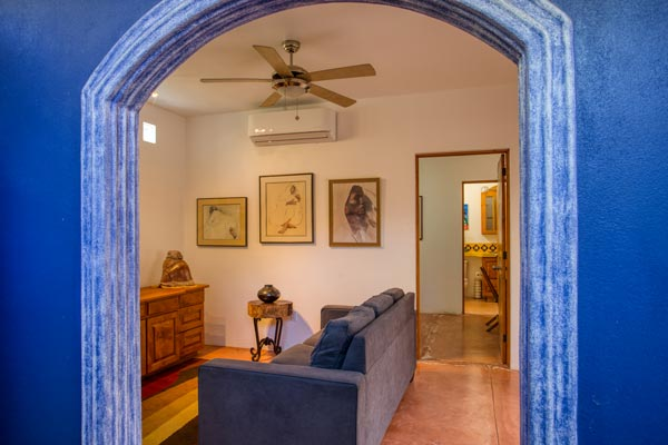 blue arch opening into living room with museum lighting and art on wall