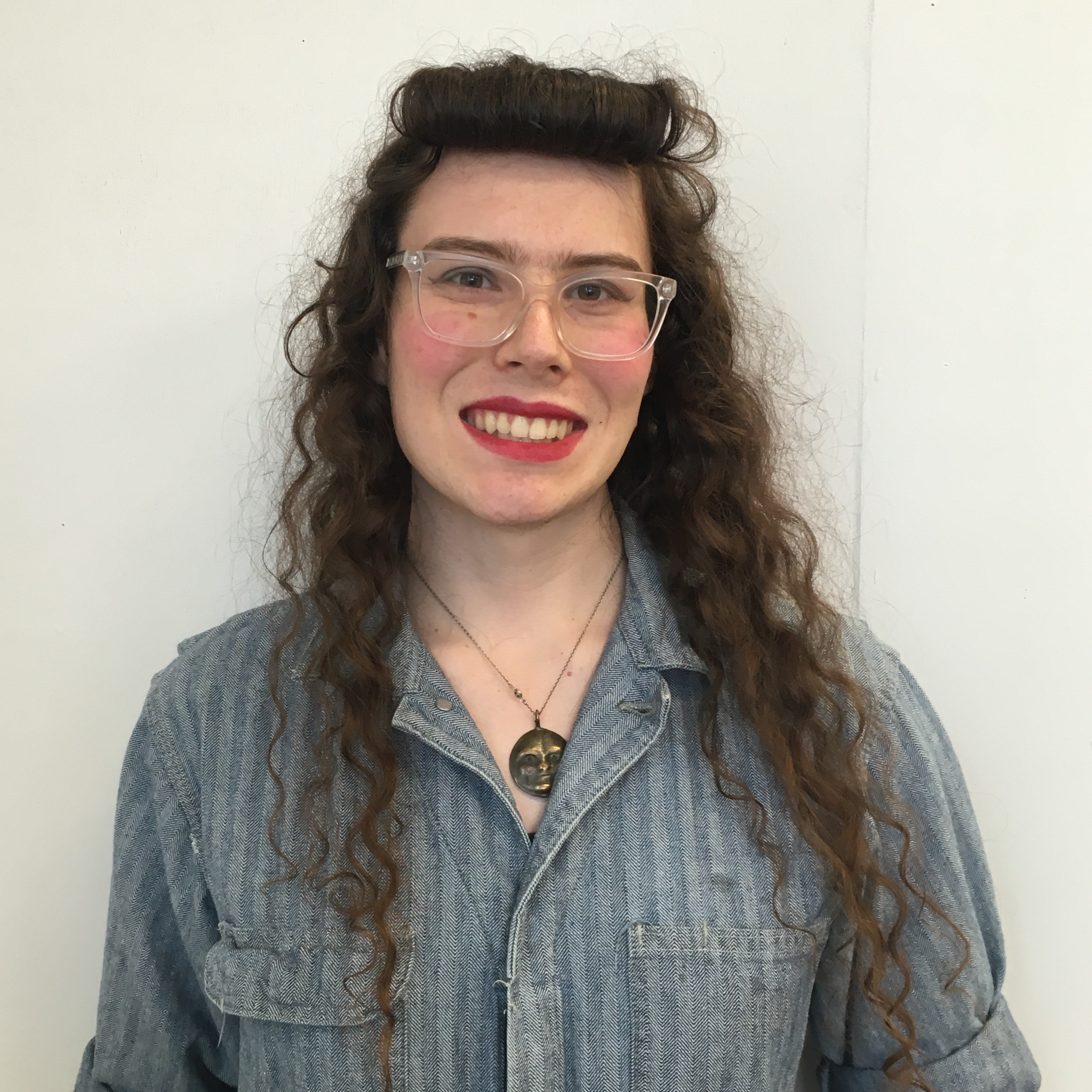 A headshot of Morgan, a young white woman with long curly brown hair, smiling at the camera. She is wearing glasses, red lipstick, a bronze necklace, and a blue boiler suit.