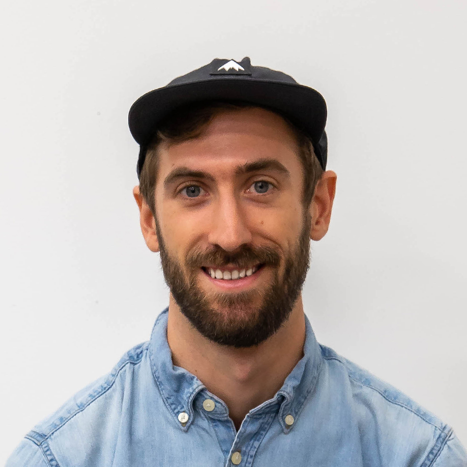 Tyler Hawkins wearing a hat, smiling at the camera. He is wearing a blue buttoned denim shirt.