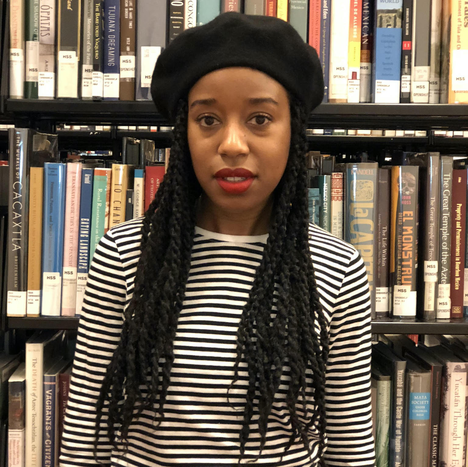Simone Wright wearing a black hat and striped t-shirt smiling at the camera in front of a bookshelf.