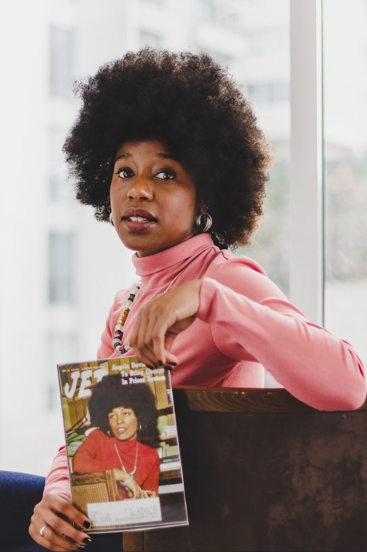 A photo of Simone in a pink turtle neck holding a magazine with Angela Davis on the front. Simone's hair matches Angela Davis'.
