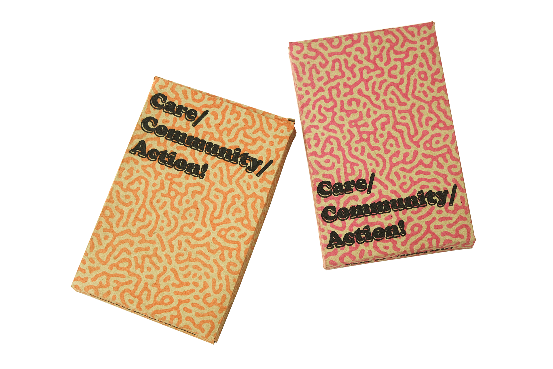"""Two small cardboard boxes printed in a pattern of organic lines, one fluorescent pink and one fluorescent orange, on a transparent background. Both boxes have """"Care Community Action!"""" printed in black on their front."""