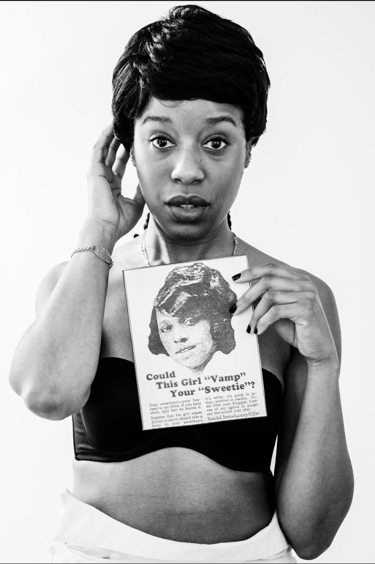 """A photo of Simone holding a photo with a photo of someone which says below """"Could this girl vamp your sweetie?"""". Simone's hair matches the hair on the image she is holding"""