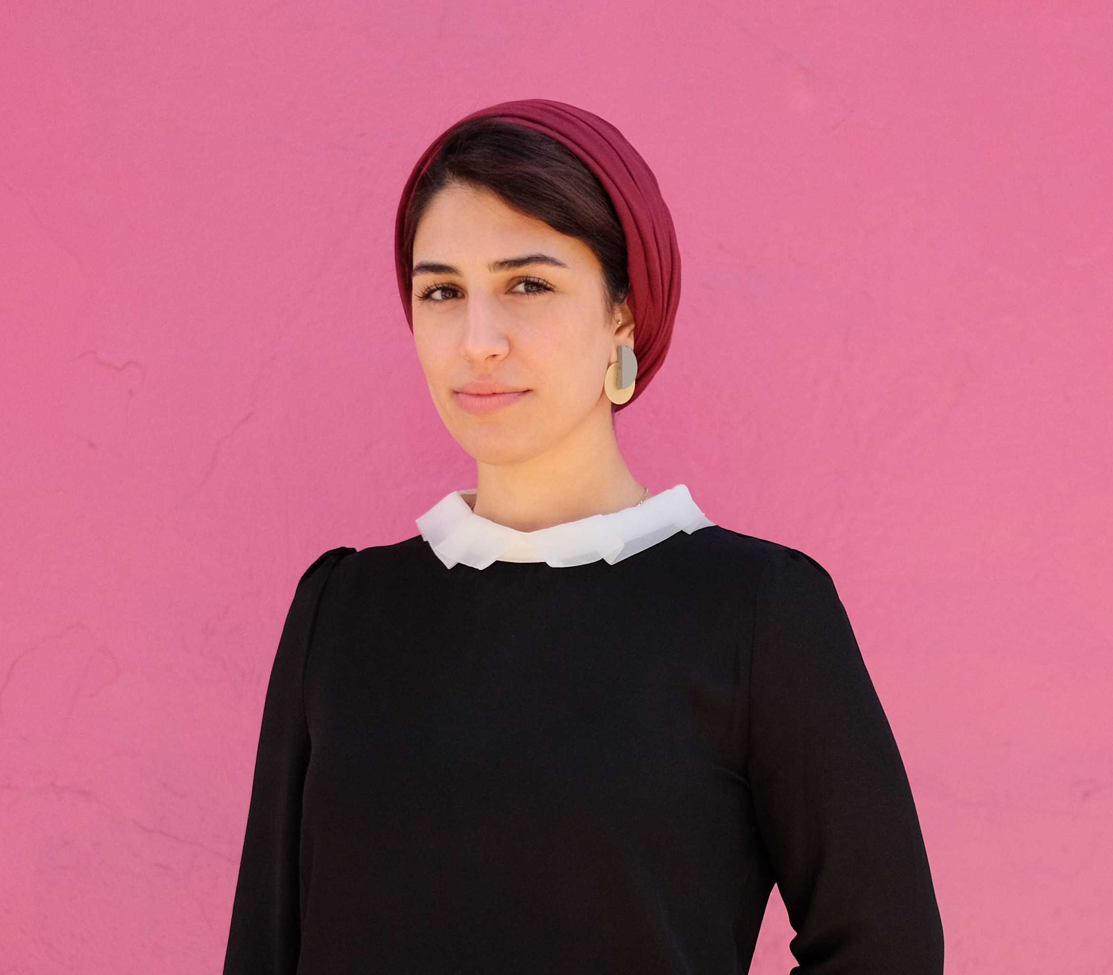 Hanieh wearing a navy sweater with a white collar in front of a pink background smiling.