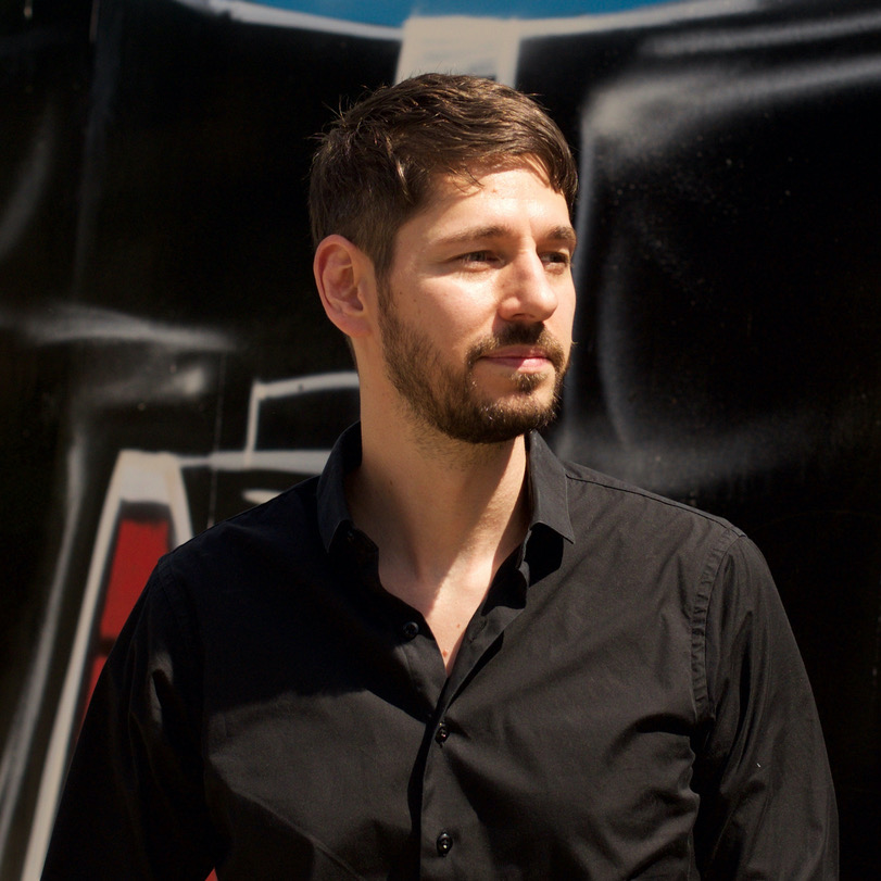 Lee wearing a black buttoned shirt and looking off camera.