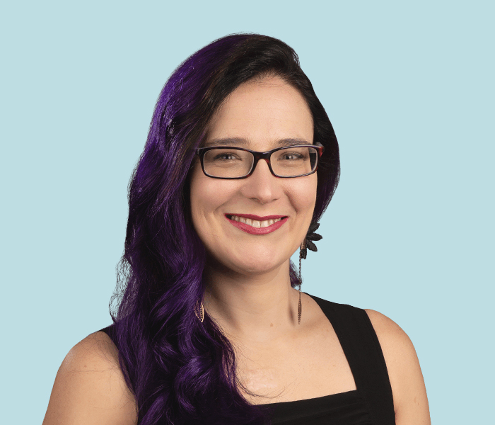 Deborah wearing glasses and a black top in front of a light blue background.