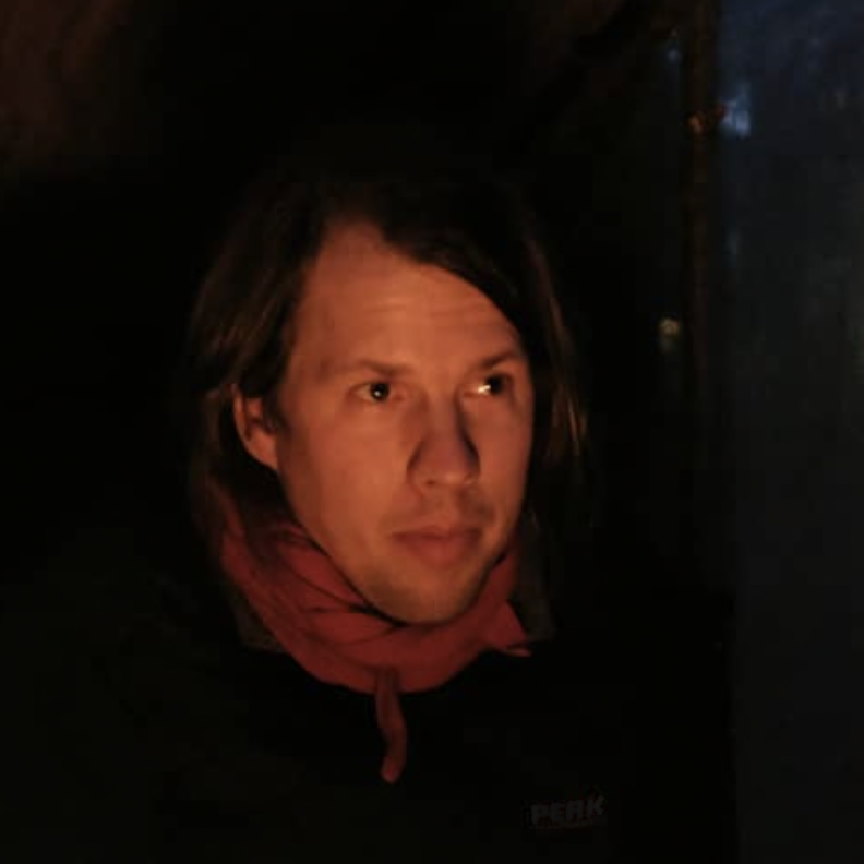 Brad looking off camera as his face is illuminated by a dim light.
