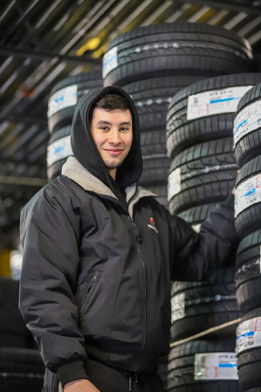 male employe standing in front of tires smiling