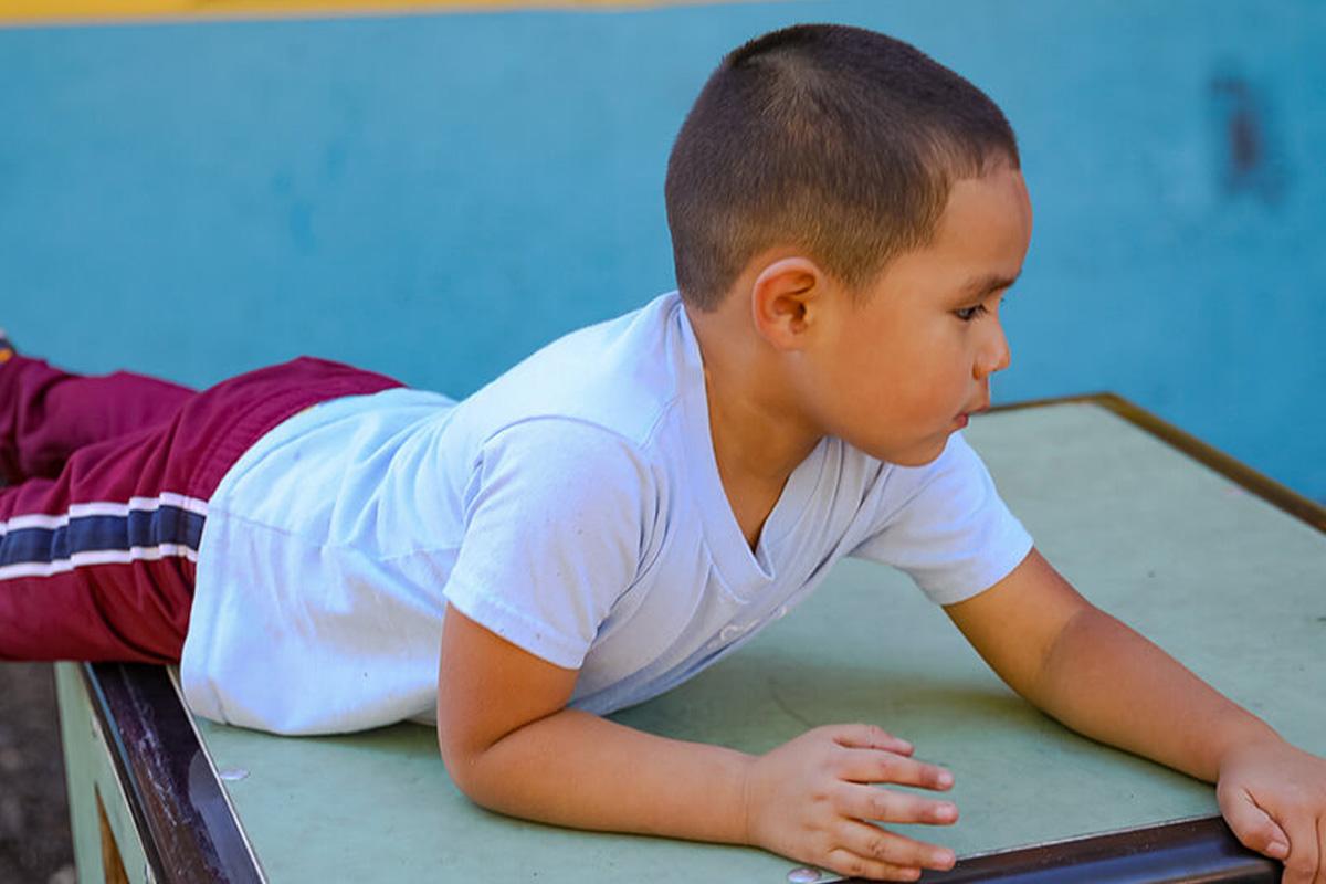 Niño latino jugando en una caja
