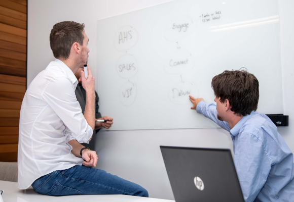 Two men writing on a whiteboard and discussing the content