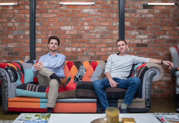Two business men sit on a couch