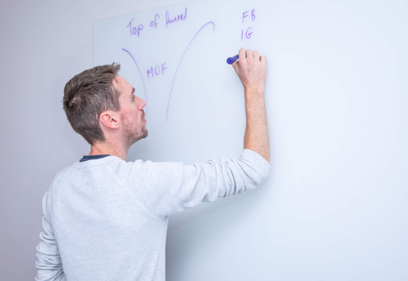 A man writing on a whiteboard