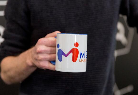 A man holding up a mug