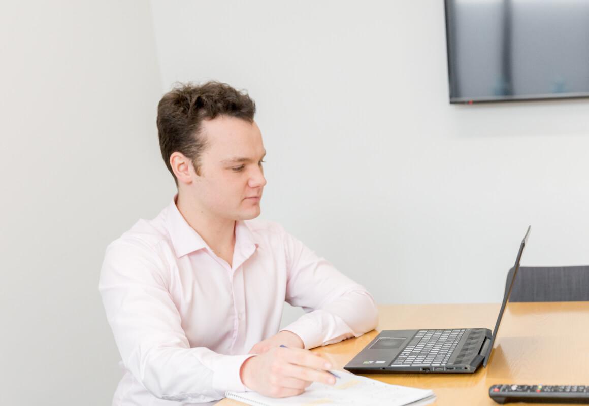 A man in a pink dress shirt sitting at a computer