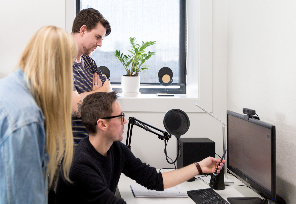 Three people standing around a computer, staring at the screen