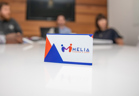 Melia Marketing's business card with staff members in the background